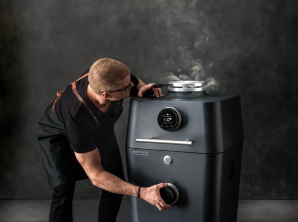 """Everdure 4k Electric Ignition Smart BBQ - Graphite - <div>  <hr />  <h3 class=""""list-title"""">Airflow Control</h3> <p class=""""body-text medium"""">The 4K's unparalleled airflow control system makes turning the heat up or slowing it down a unique experience. Both top and bottom vents are precisely numbered for a more balanced and responsive flow of air.</p>  <h3 class=""""list-title"""">The Anatomy</h3> <p class=""""body-text medium"""">The 4K has all the hardware you need. 2 x matte vitreous enamel grills; 2 x 304 grade stainless steel grills; a 33cm cordierite pizza stone / heat deflector; water container; internal light; grill tongs; and charcoal tongs are all included.</p>  </div> <div> <h3 class=""""list-title"""">Sealed, Safe and Sound</h3> <p class=""""body-text medium"""">Striking both inside and out, the 4K is a solid machine constructed from diecast aluminum and thick gauge metal. Our unique insulation design reduces heat transfer to the external body sides and front.</p>  <h3 class=""""list-title"""">Real Time Results</h3> <p class=""""body-text medium"""">With 2 discreet probes in the hood and 4 removable probes internally, the 4K takes outdoor cooking to another level. Displayed beautifully, all data can be accessed via bluetooth to our free app which is also packed full of hints, tips, recipes and alerts.</p>  </div> <div> <h3 class=""""list-title"""">Touch Glass, Get Flame</h3> <p class=""""body-text medium"""">The 4K's outer body is complete with touch glass display; putting fire at your fingertips.</p>   <hr /> <p class=""""body-text medium""""></p>  </div>"""