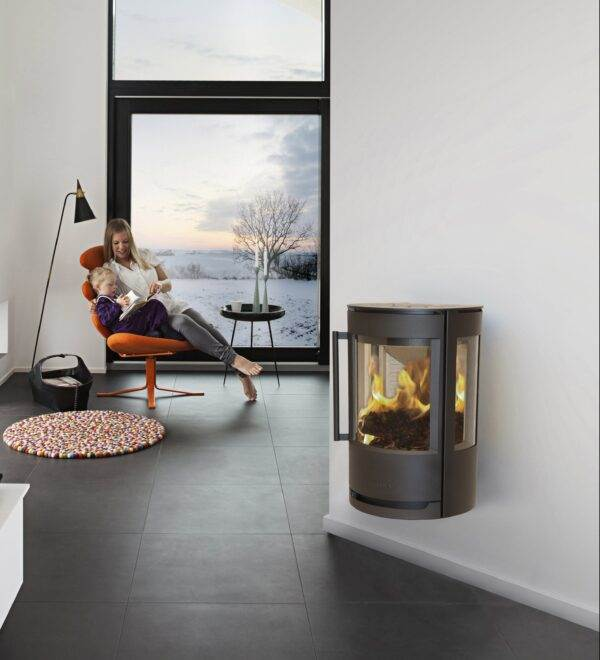 Wiking Luma 1 - WIKING Luma 1 and 2 are the lowest wall-mounted stoves in the WIKING Luma series. But this does not prevent the firewood from being fully utilised, to the benefit of the user and the environment. Both models have a large stove glass set in a solid castiron door, and Luma 1 also has wide side windows, so you can enjoy the view of crackling flames from all angles. Both WIKING Luma stoves are also available with a pedestal, so they can be installed on the floor.