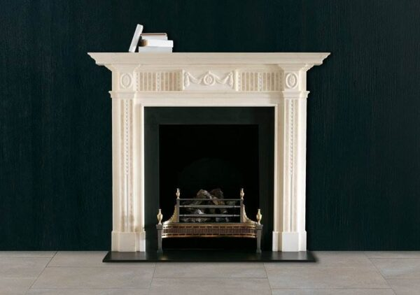 The Albemarle - A neo-classical chimneypiece in statuary marble with carved centre tablet and corner blockings. The jambs and frieze panels are inlaid with Etruscan gold marble.
