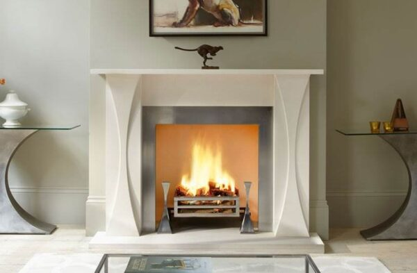 The Faulkner - The Faulkner surround is carved in limestone with the distinctive sweeping design in the pilasters reflected in the accompanying Faulkner polished steel fire dogs.