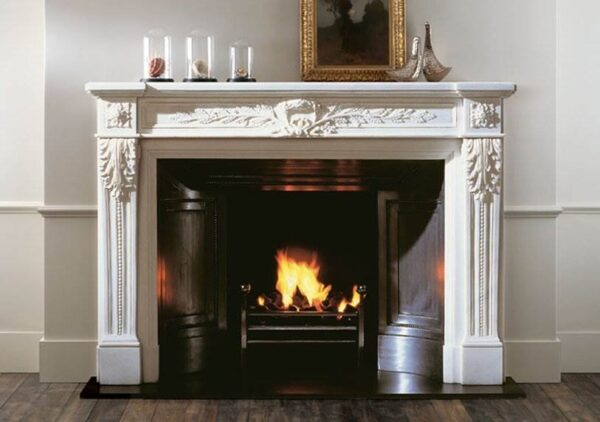 The Fontainebleau - A French style marble chimneypiece of 18th century design having carved rosettes on the corner blocks above console jambs headed by Acanthus leaf carvings and incorporating carved wreath and trailing foliage to the frieze.