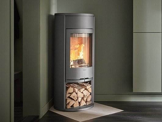 Contura 610 Style - Contura 610 Style is the smallest model in the grown up 600 series. For example, you can choose a cast iron or glass door, surround in black, grey or white metal, log compartment or door, front cover or warming shelf above the door and accessories such as a heat retaining powerstone, hotplate and fan. One attractive and practical new feature is log storage at the side of the stove.