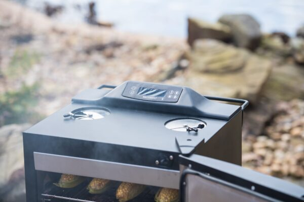 """Masterbuilt 30"""" Bluetooth Digital Electric Smoker - With the Masterbuilt 30"""" Bluetooth Digital Electric Smoker you can monitor your masterpiece using Bluetooth Smart technology and achieve perfect results with the built-in meat probe thermometer. Dabble in flavour using a variety of wood chips in the patented side wood chip loading system. Finish ribs, crisp chicken wings, or sear burgers using the innovative grill and finish element. With four chrome-coated smoking racks, there is plenty of room to smoke up to 6 chickens, 2 turkeys, 4 racks of ribs, or 4 pork butts. Master the art of smoking with Masterbuilt!"""