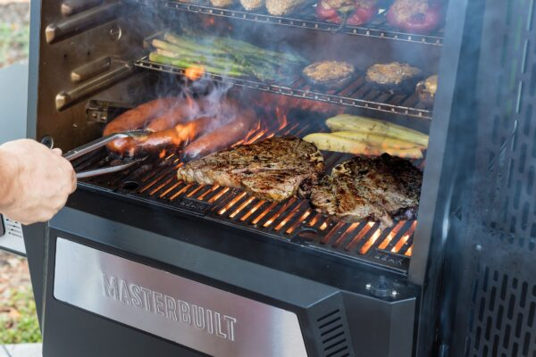 Masterbuilt Gravity Series 560 Digital Charcoal Grill & Smoker - With the Gravity Series? 560 Digital Charcoal Grill + Smoker by Masterbuilt, you can smoke, grill, sear, bake, roast and so much more.? Set the temperature on the digital control panel or your smart device and the DigitalFan? maintains the desired cooking temperature.? The GravityFed? charcoal hopper holds over 12 hours of charcoal and gravity ensures you have constant fuel to the fire.? The reversible cast-iron grates are perfect for smoking or searing and in just 13 minutes this grill can reach 700?F.? Master the art of charcoal grilling and smoking with Masterbuilt.