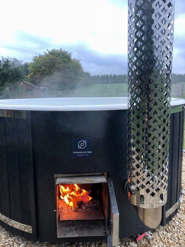 Cotswold Wood Fired Eco Tub - The Winchcombe - 8/9 Person Tub - This Winchcombe Deluxe wood fired Hot Tub is the largest of the range and is perfect for larger family's and couples who love to entertain with friends and family. Hand crafted in Denmark this is built for nothing else than carefree relaxation, perfect for any garden, patio, glamping pod or courtyard setting… available in different colours and spec finishing's.