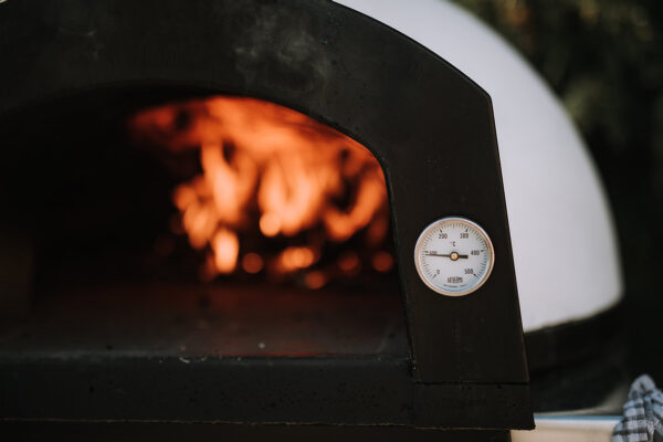 Etna 600 Pizza Oven & Stand - Etna 600 Pizza Oven & Stand also comes with a free paddle <strong>A<em>Brand New</em><em></em>product available at Topstak!</strong> The Etna 600 Wood fired Pizza Oven is the embodiment of a classic Italian artisan pizza oven. Hand built with pride, beautifully designed and compact, the Etna 600 artisan wood fired pizza oven is not only perfect for making artisan pizzas at home, but will also make a wonderful centrepiece in any garden. Based on the traditional Italian wood fired oven shape, the Etna 600 oven is the most aesthetically pleasing on the market. With the ability to reach temperatures of around 500°c, our oven will cook 1 large or 2 x 10 inch pizzas in under 2 minutes. Its heat retaining material will keep a consistent temperature for approximately 1 hour 30 minutes. But don't think that pizzas are your only party piece here! The Etna 600 will happily bake bread, slow roast your favourite meats and vegetables, smoke fish or ribs and even bake a batch of brownies! There really isn't a lot the Etna 600 won't allow you to cook. As the heat from the oven subsides, you can all gather round and use its warmth as a patio heater as the night draws in.